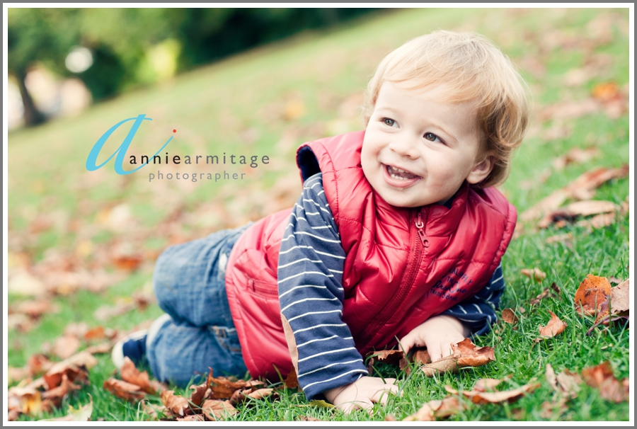 A two year old boy rolling down the hill by the river at by the river at Canbury Gardens in Kingston upon thames