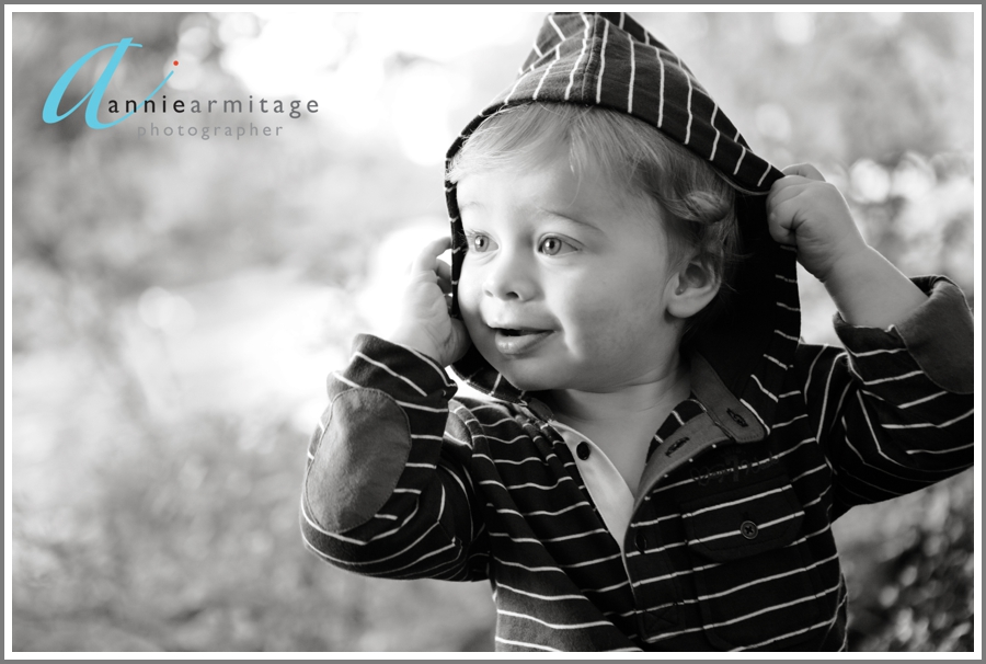 A 2 year old boy smiling by the river by the river at Canbury Gardens in Kingston upon thames