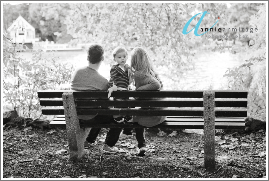 A two year old boy and his parents sitting on a bench at Canbury Gardens in Kingston upon thames