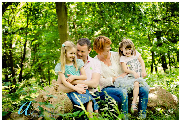 A colour picture of a family sitting on a log in a kingston park with a mum and day and two young girls