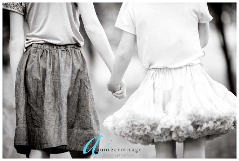 a black and white picture of two young girls holding hands with a tutu