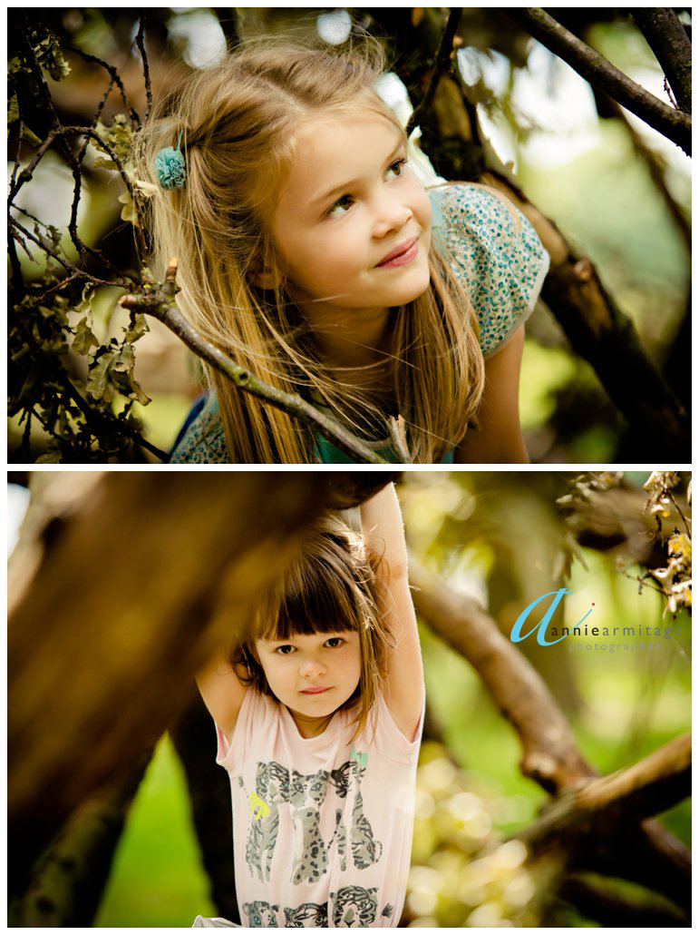 a blonde girl with a blue hair clip peeping through the branches of a den in a park in kingston upon thames and a little girl wearing a pink t shirt looking at the camera in the woods in the park