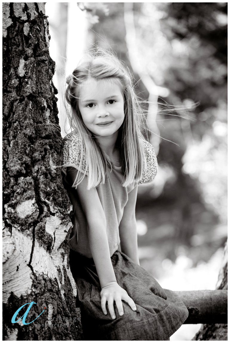a black and white image of a young girl sitting in a tree in a park in kingston upon thames