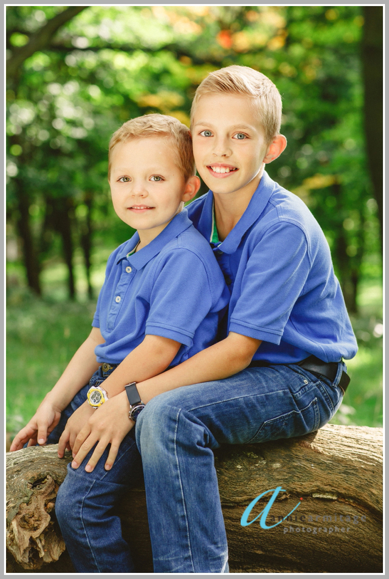 Two swedish boys who live in London sitting on a log in the woods wearing blue tops and smiling for the photographer