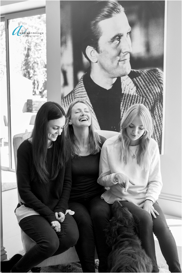 a black and white photograph of a mother and two daughters laughing with a picture of Kirk douglas behind and the two dogs at their feet