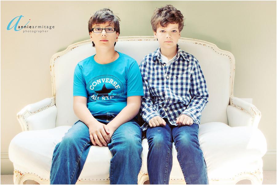 two boys sitting on an antique cream sofa