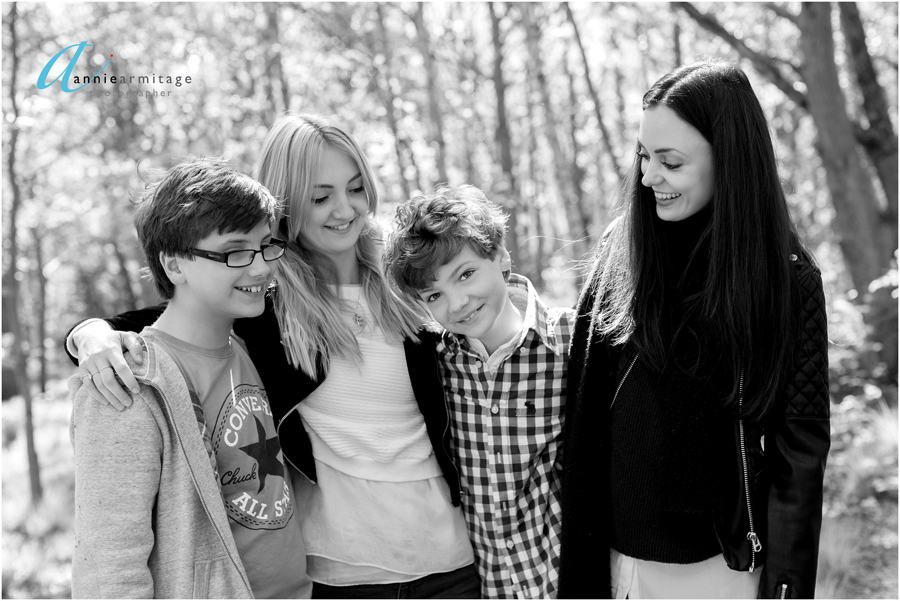 a black and white picture of four siblings laughing together on wimbledon common