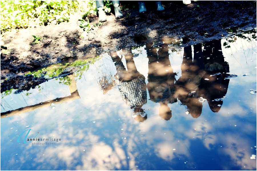 a reflection of the family in a muddy puddle on Wimbledon Common