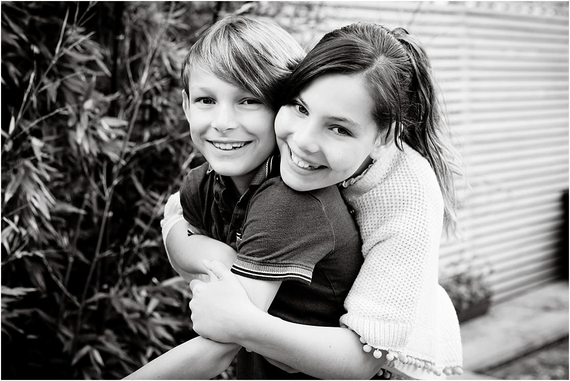a black and white picture of a brother and sister giving each other a hug at their home in Barnes southwest london SW13