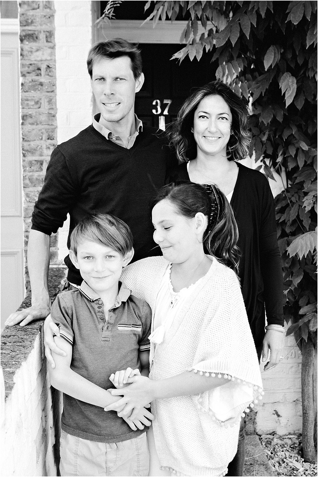an image of a family in black and white standing on their front doorstep of their house in Barnes SW13 with the wisteria on the side of the doorway