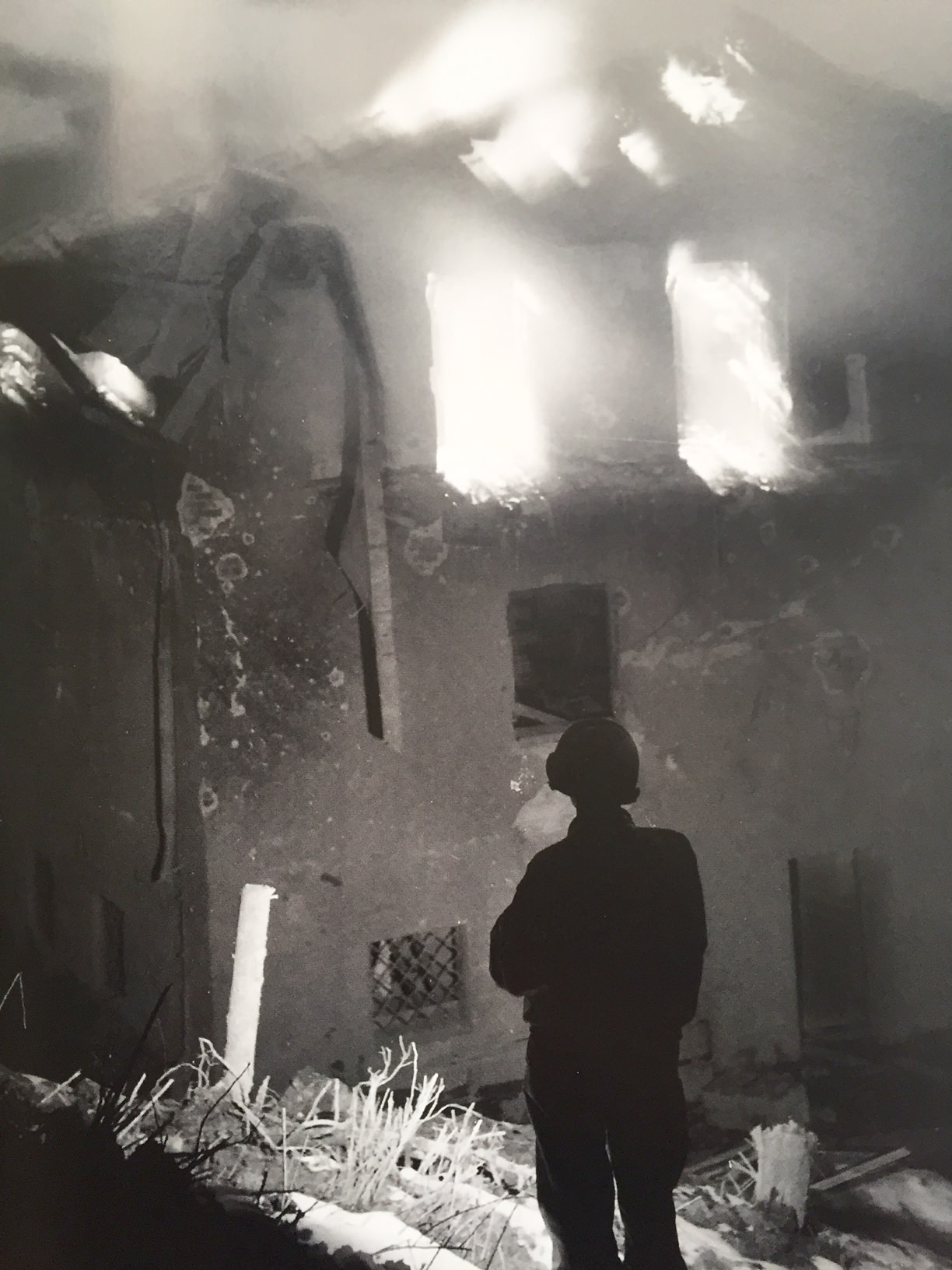 a woman looking a burning building in the 2nd world war