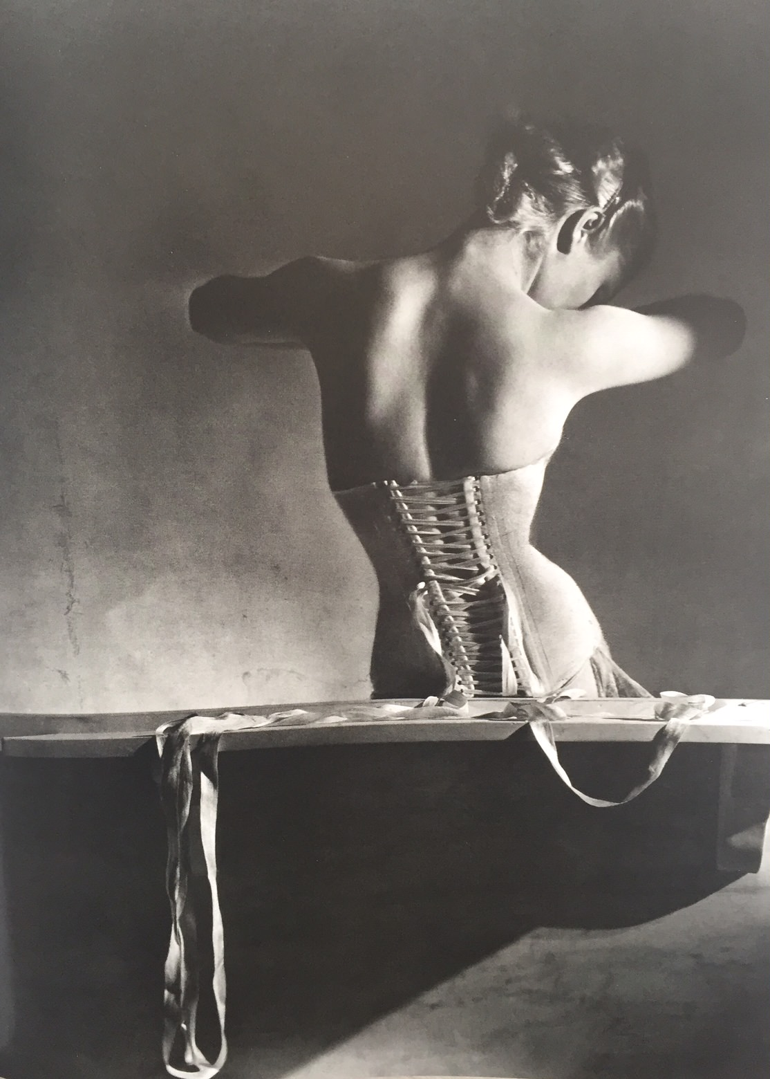 a woman with a back to the camera wearing a boned lace up corset in black and white