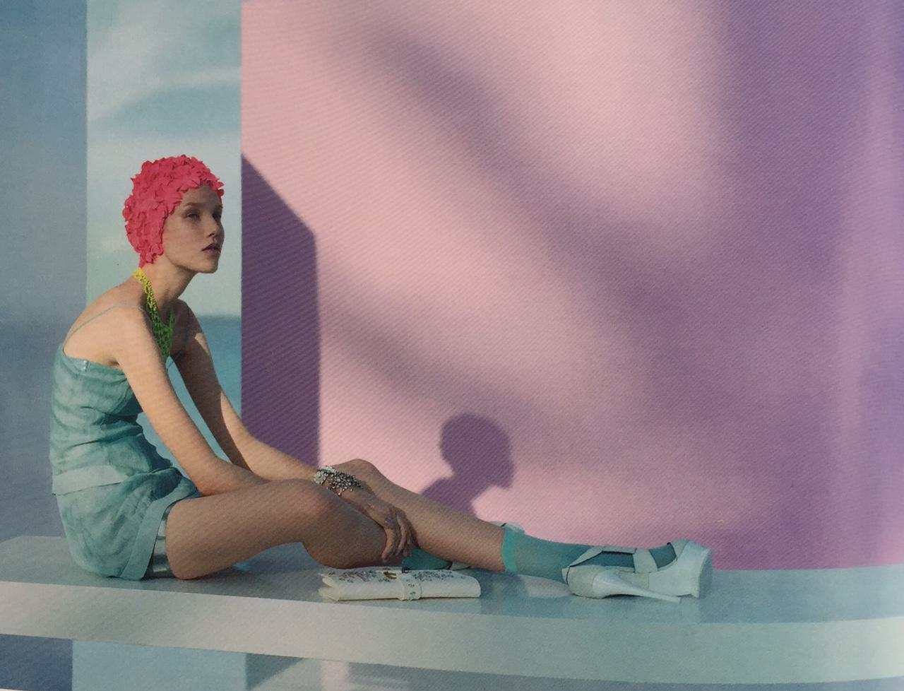a woman wearing a bathing hat sitting against a pink wall in evening light