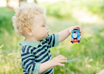 a blonde toddler looking at his Thomas the tank engine in the park in Esher