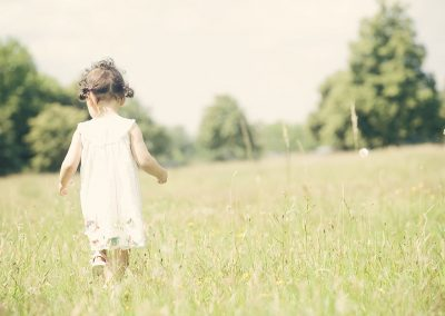 a little girl walking through a meadow at Ham House in Richmond upon Thames