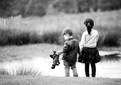 a sister and brother hold hands looking at pond with the boy holding his teddybear in Claygate
