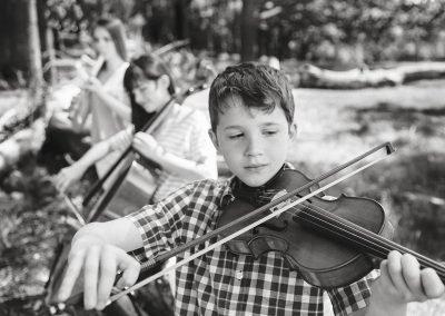 three children play the violin, cello and recorder in the park in Twickenham