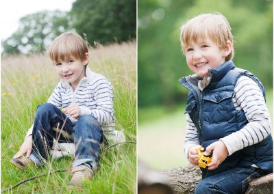 A little boy sits in the grass and laughs wearing blue jeans in Fulham