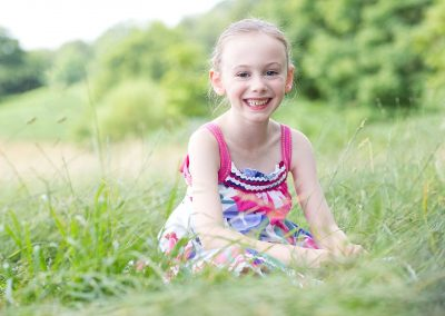 a young girl sits in the grass smiling at the camera wearing a pink dress in Kew