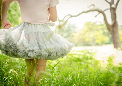 a young girl wearing a blue tutu in the grasses in a park in woods in Cobham