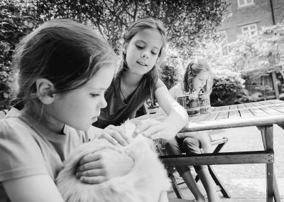 three girls at home in Kew looking at a persian cat