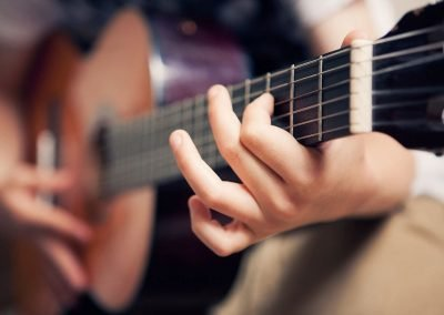 child's fingers on a the frets of a guitar
