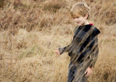 a boy wearing black walks through long grass in Esher