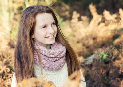 a ten year old girl with auburn hair laughs in the bracken in autumn in Cobham