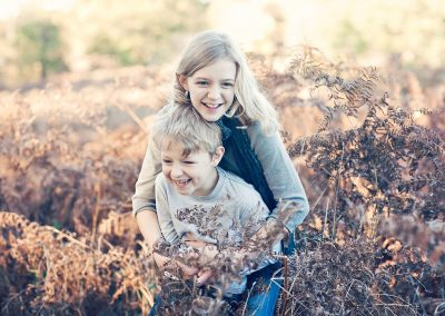 a blonde brother and sister laugh in autumn bracken and ferns in Thames Ditton