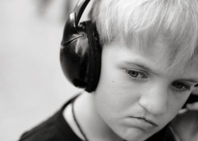 a seven year old boy listens to his music with headphones on in Clapham, London