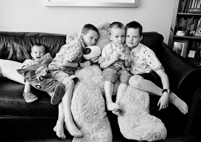 Four young brothers sit on a big teddybear in Wimbledon