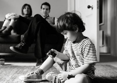 a four year old boy plays with his trains with his parents looking on behind in Kew