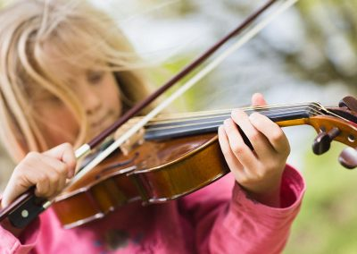 a blonde girl plays the violin in the park in Sheen, London