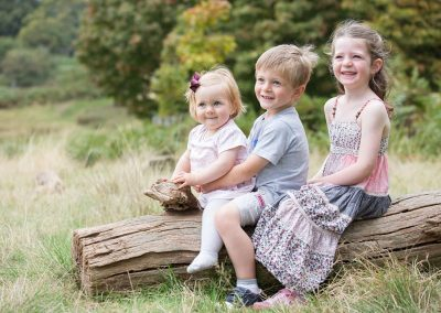 three young children sit on a log in the park in Richmond upon Thames