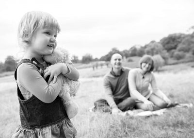a 3 year old girl holding her teddybear with her parents looking on in the park in Esher