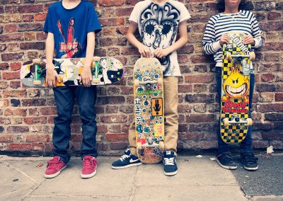 three boys with their skateboards cropped in Sheen, London