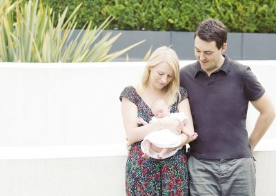 a young couple looking down at their baby girl in Richmond upon Thames against a white wall