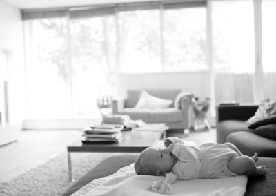 a baby lying on the sofa in a big room in Richmond upon Thames