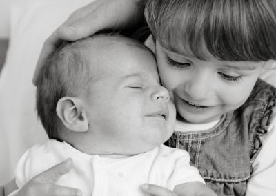 a black and white photo of a little girl and her baby brother in Wimbledon