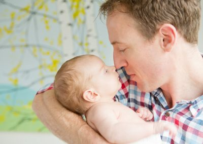 a 3 week old baby nose to nose with his daddy who is wearing a checked shirt in Esher, Surrey