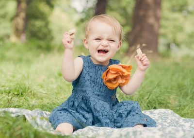 a one year old baby girl wearing a blue dress with an orange flower laughing in the grass in Richmond upon Thames