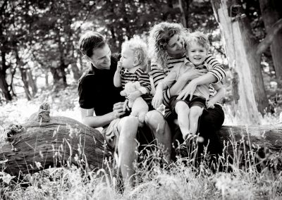 black and white images of a family with two young boys sitting on a log with their parents in a park being tickled and laughing