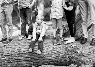 Family photography sessions with Annie Armitage in Kingston and Surrey a little sitting a log with his family
