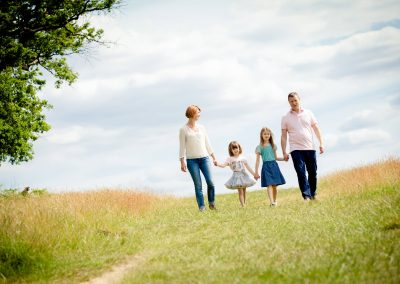 Family strolling through a field on a sunny day