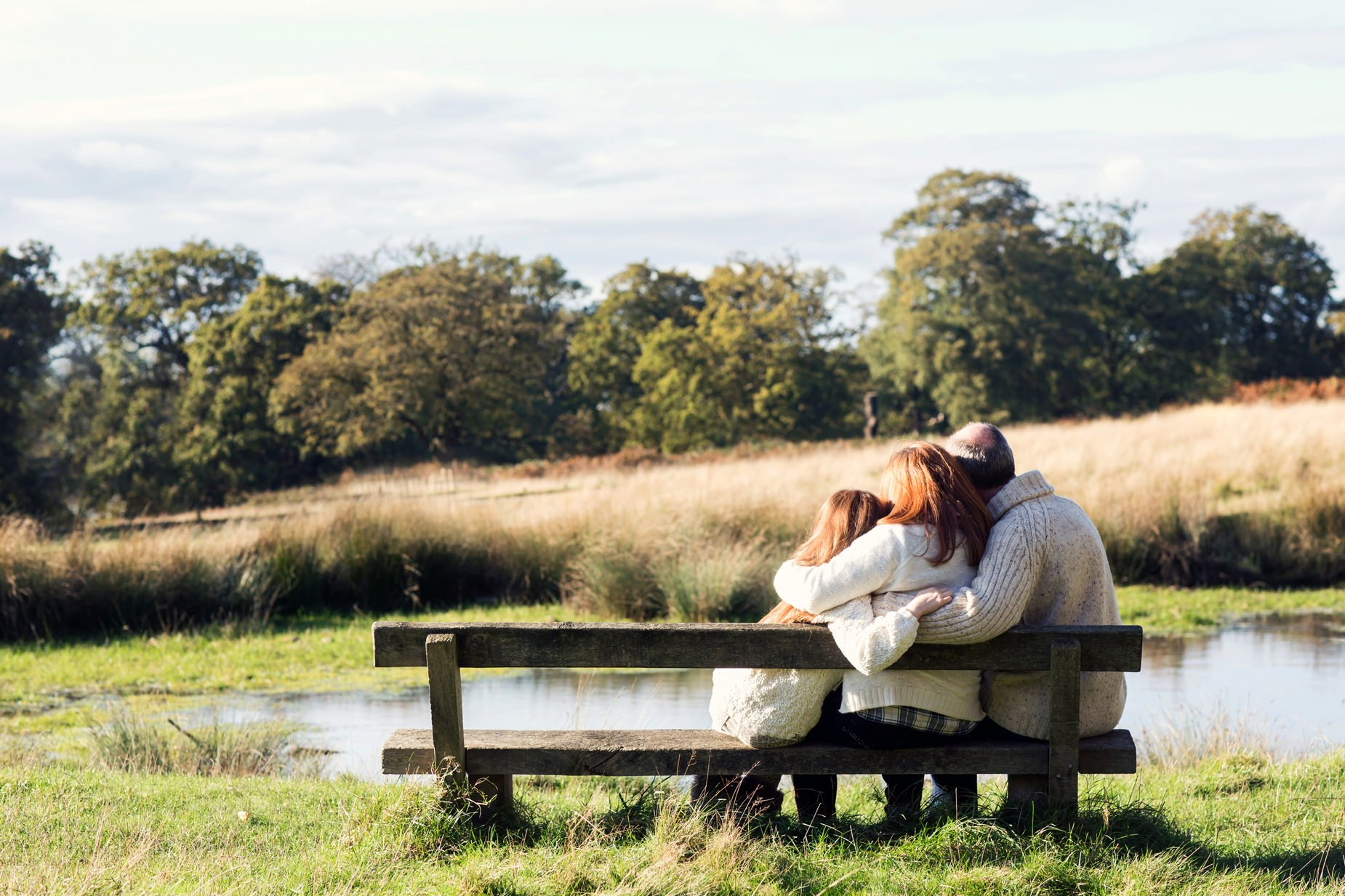 Family sitting and hugging each other on a bench in Richmond overlooking a pond