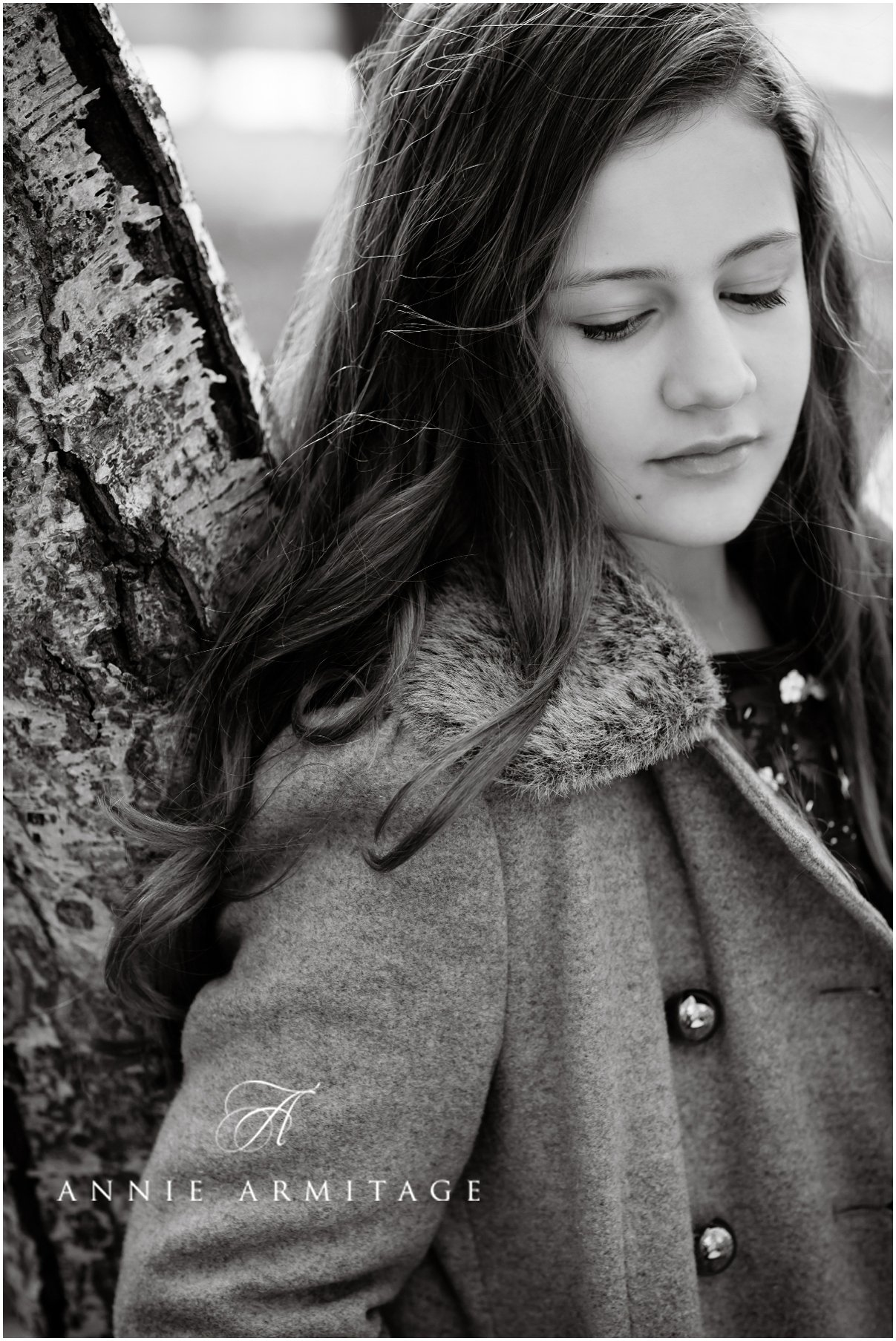 a dark haired teenager on a park photography session with her dark hair cascading and looking down