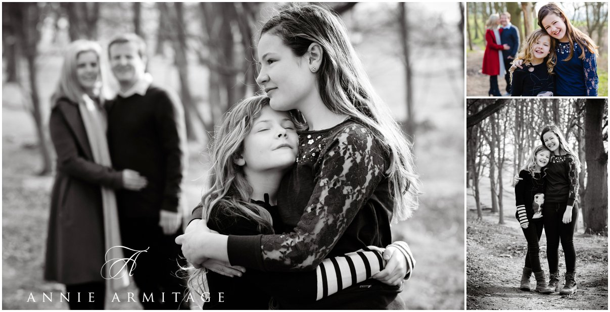 The sisters on a park family photography session cuddling each other with the parents in the background