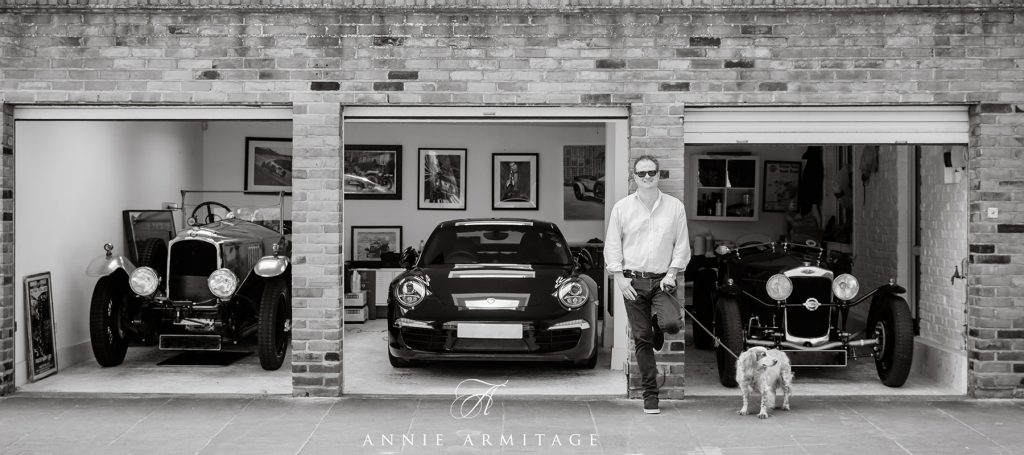 man with a garage with 3 vintage cars and his dog