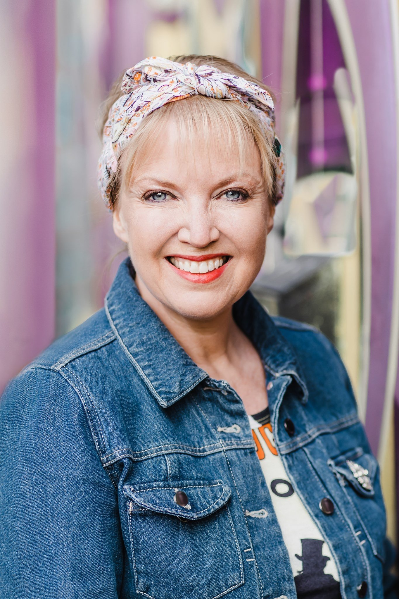 Annie Armitage photographer wearing a denim jacket and standing in front of pink mural